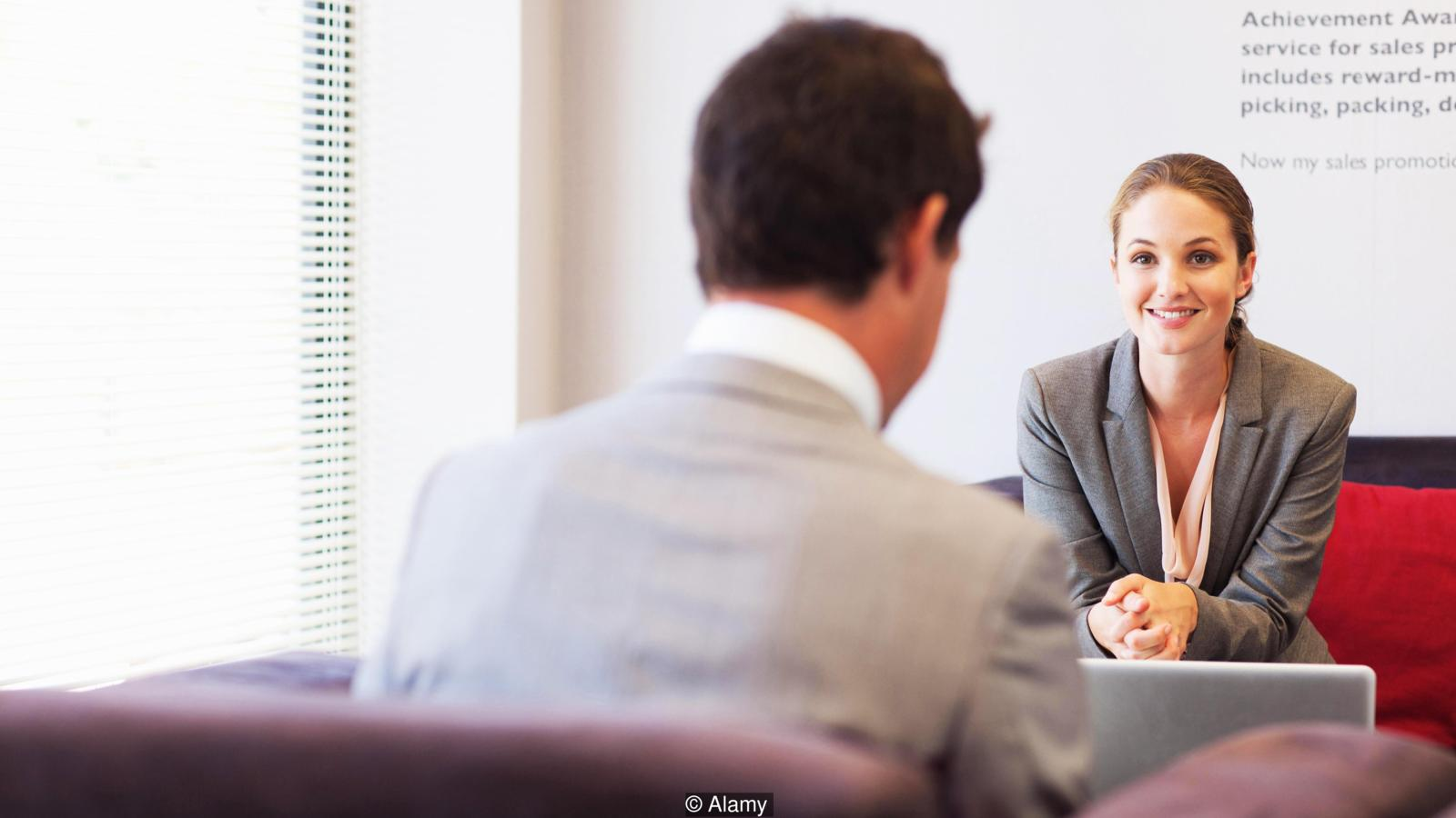 Business People Talking Face To Face In Lobby